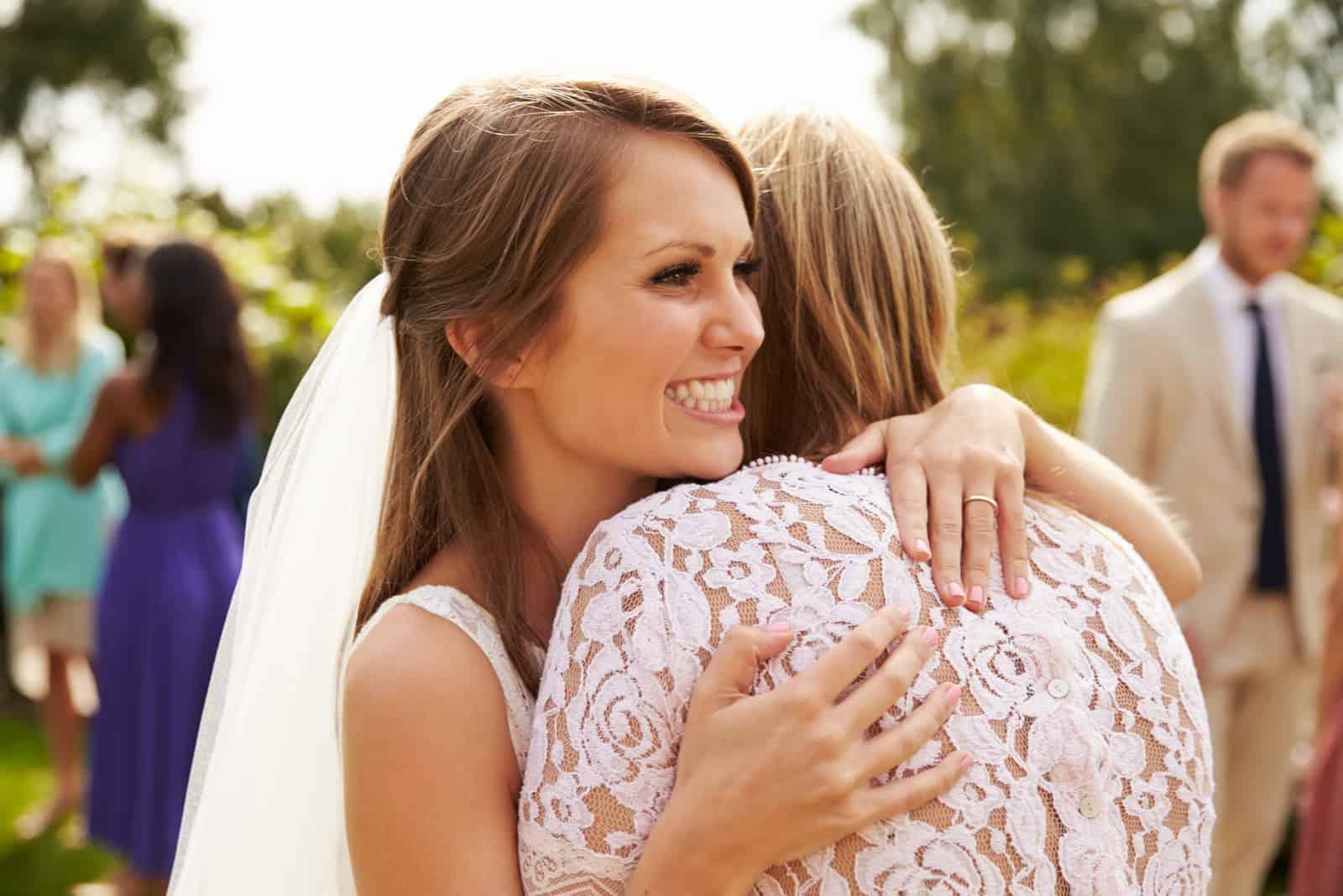 Braut, die Mutter am Hochzeitstag umarmt
