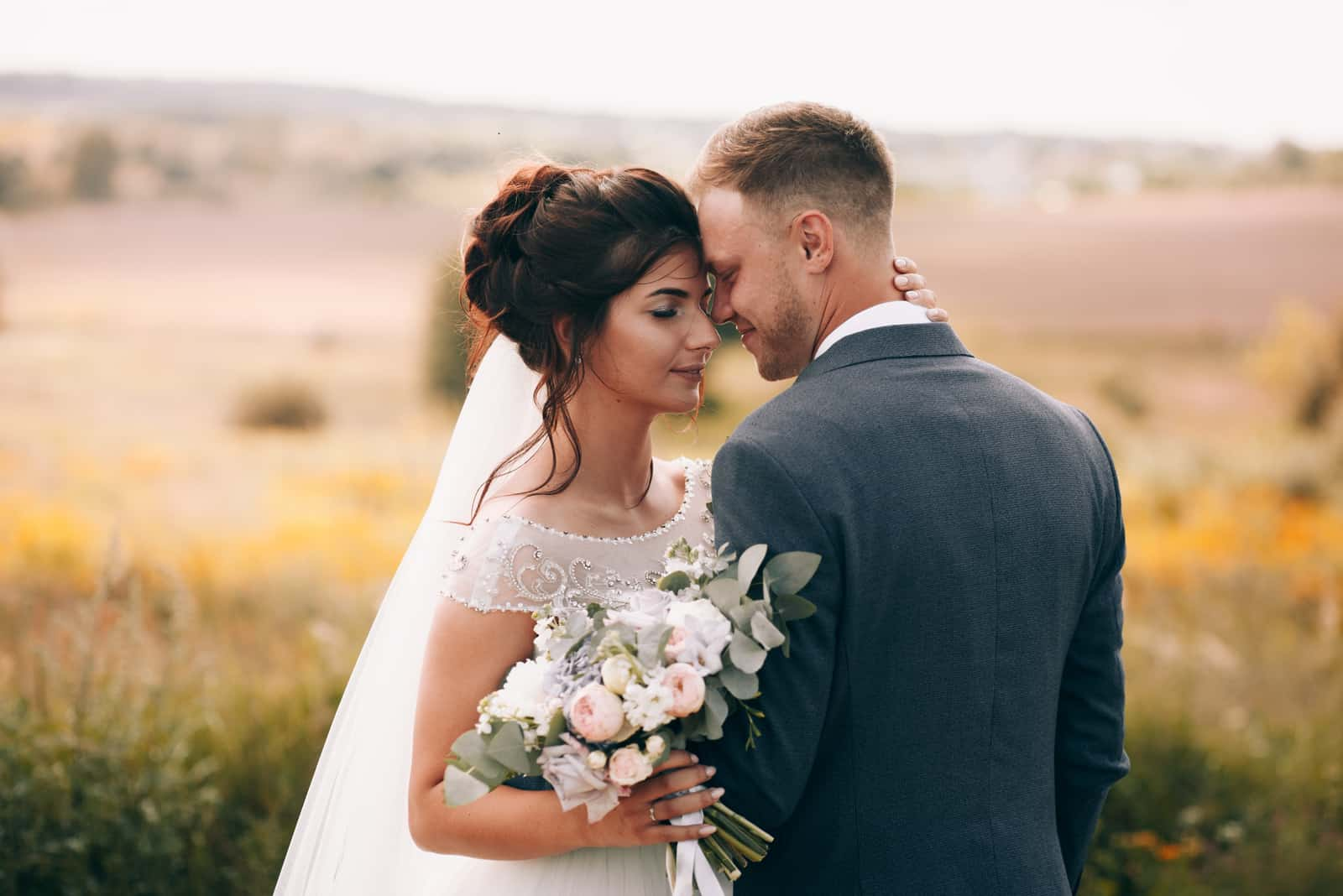 Braut und Bräutigam in einem Park küssen