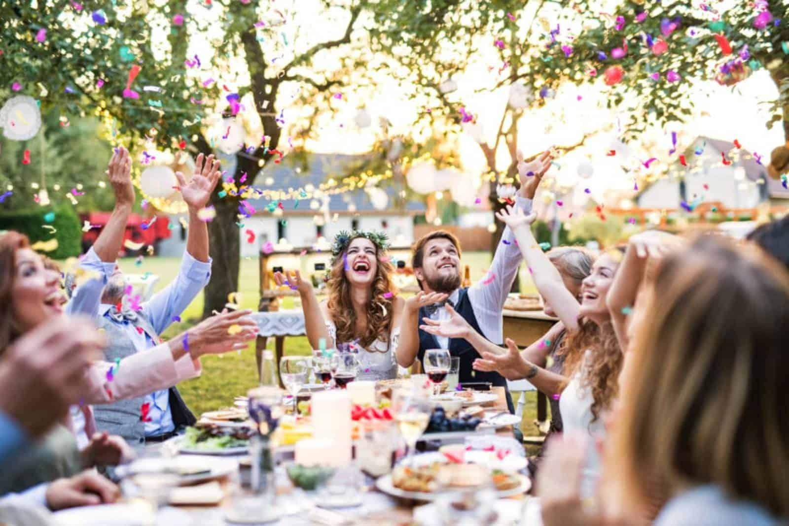 Bräutigam und Braut mit Gästen am Tisch