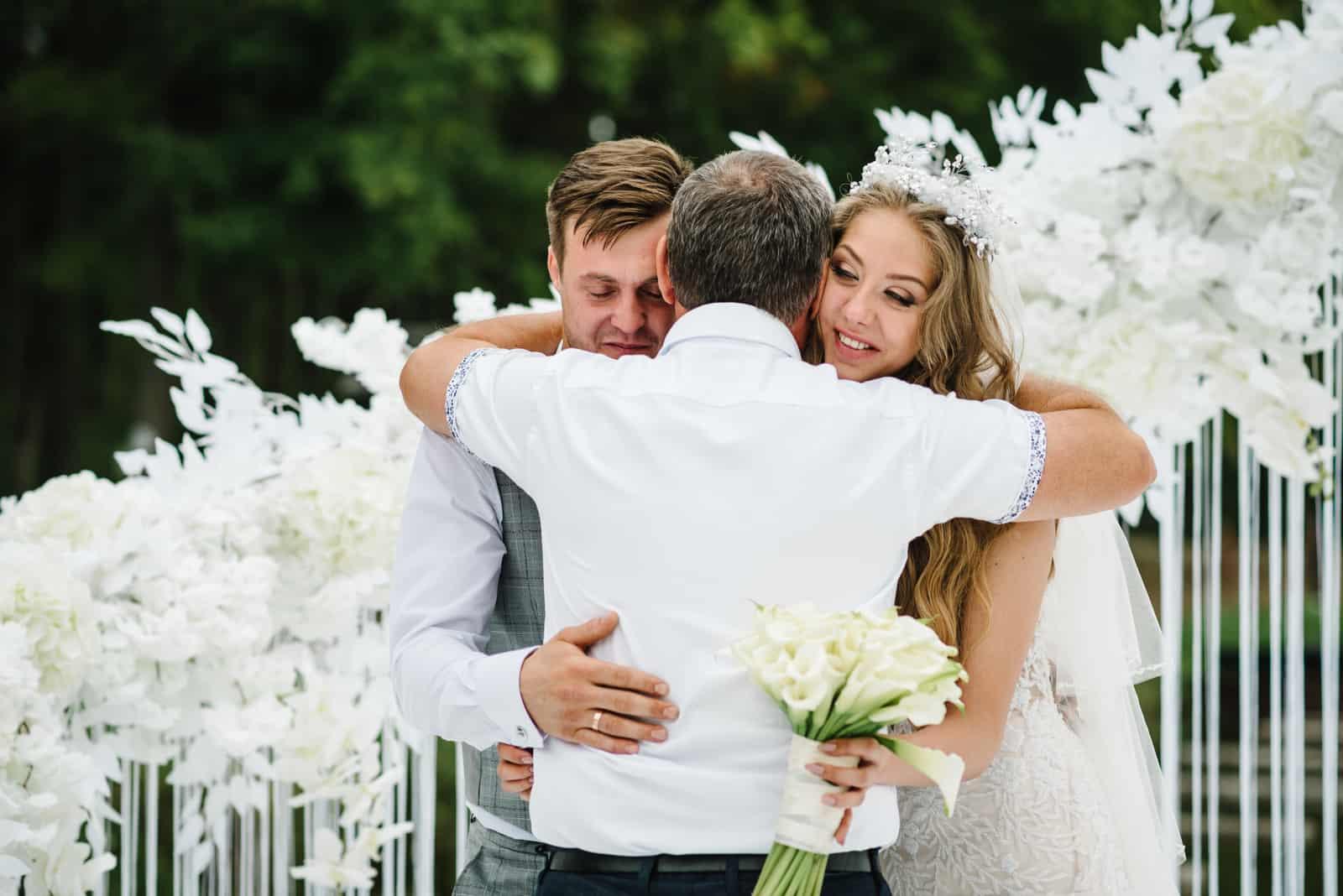 Vater gratuliert den Bräuten mit einer Ehe und Umarmungen
