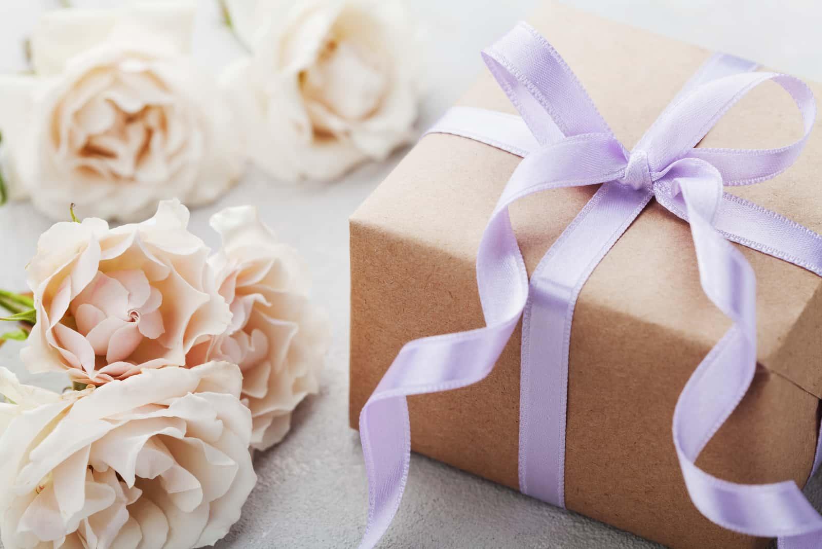 Vintage Rosenblumen und Geschenkbox mit Band auf Leuchttisch
