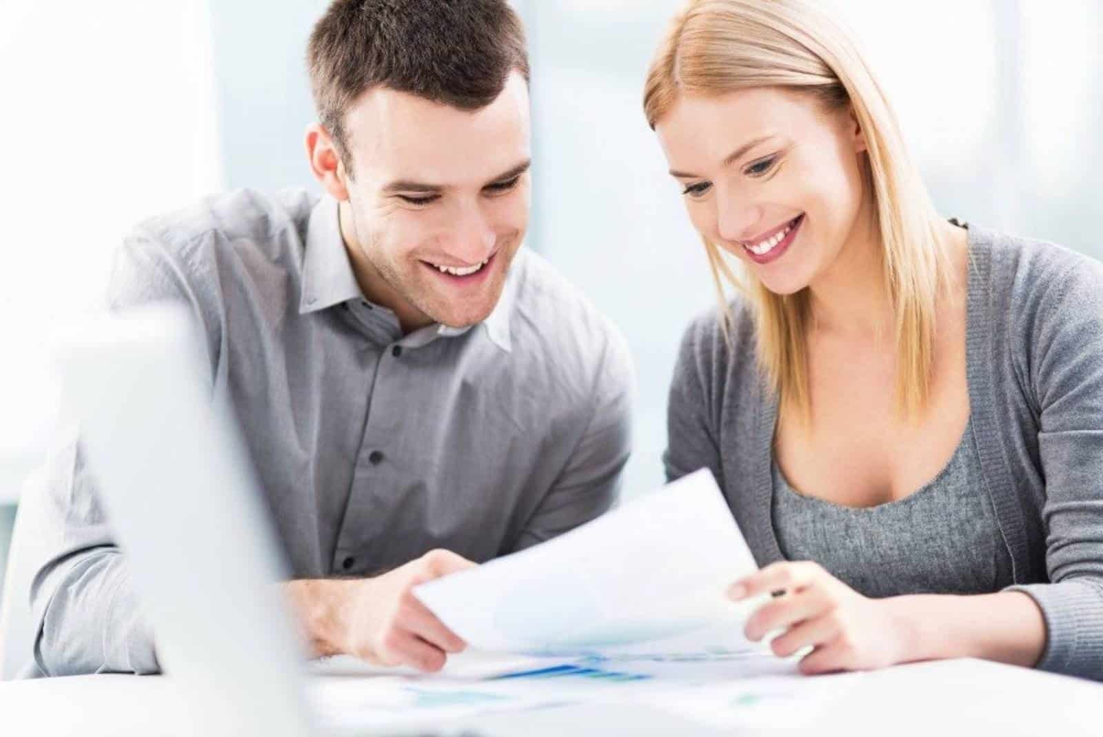 lächelndes Paar, das Papier betrachtet
