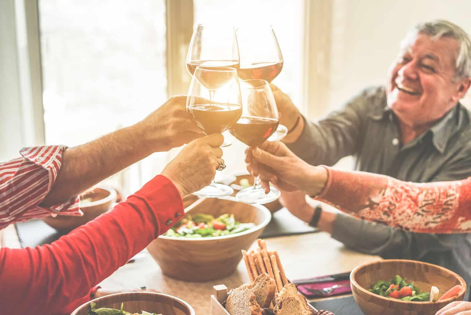Ältere Freunde jubeln mit Weingläsern beim Mittagessen zu Hause