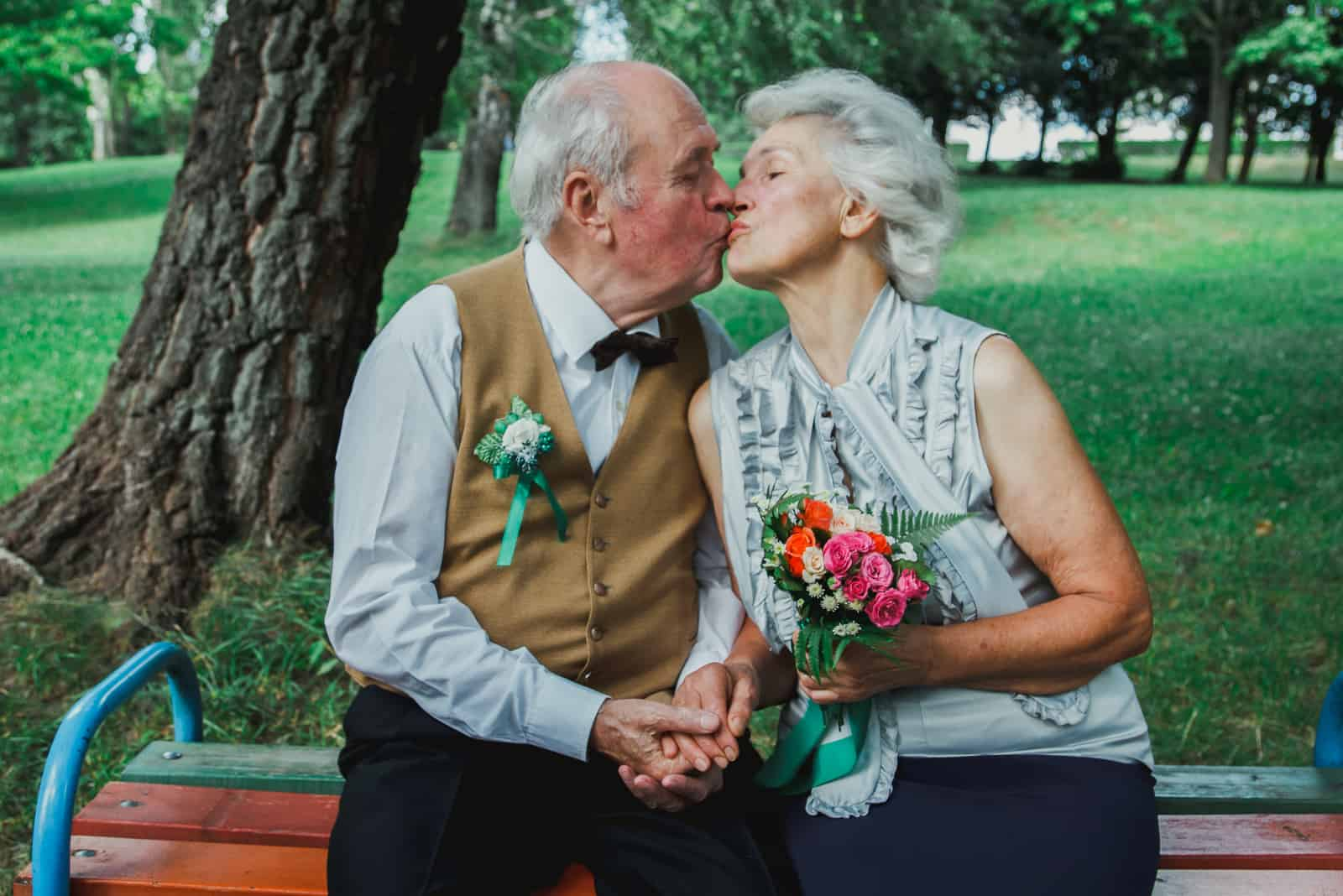 Altes Paar sitzt auf Bank im grünen Park
