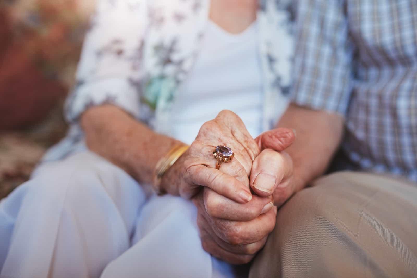 Beschnittener Schuss des Händchenhaltens des älteren Paares beim Zusammensitzen zu Hause
