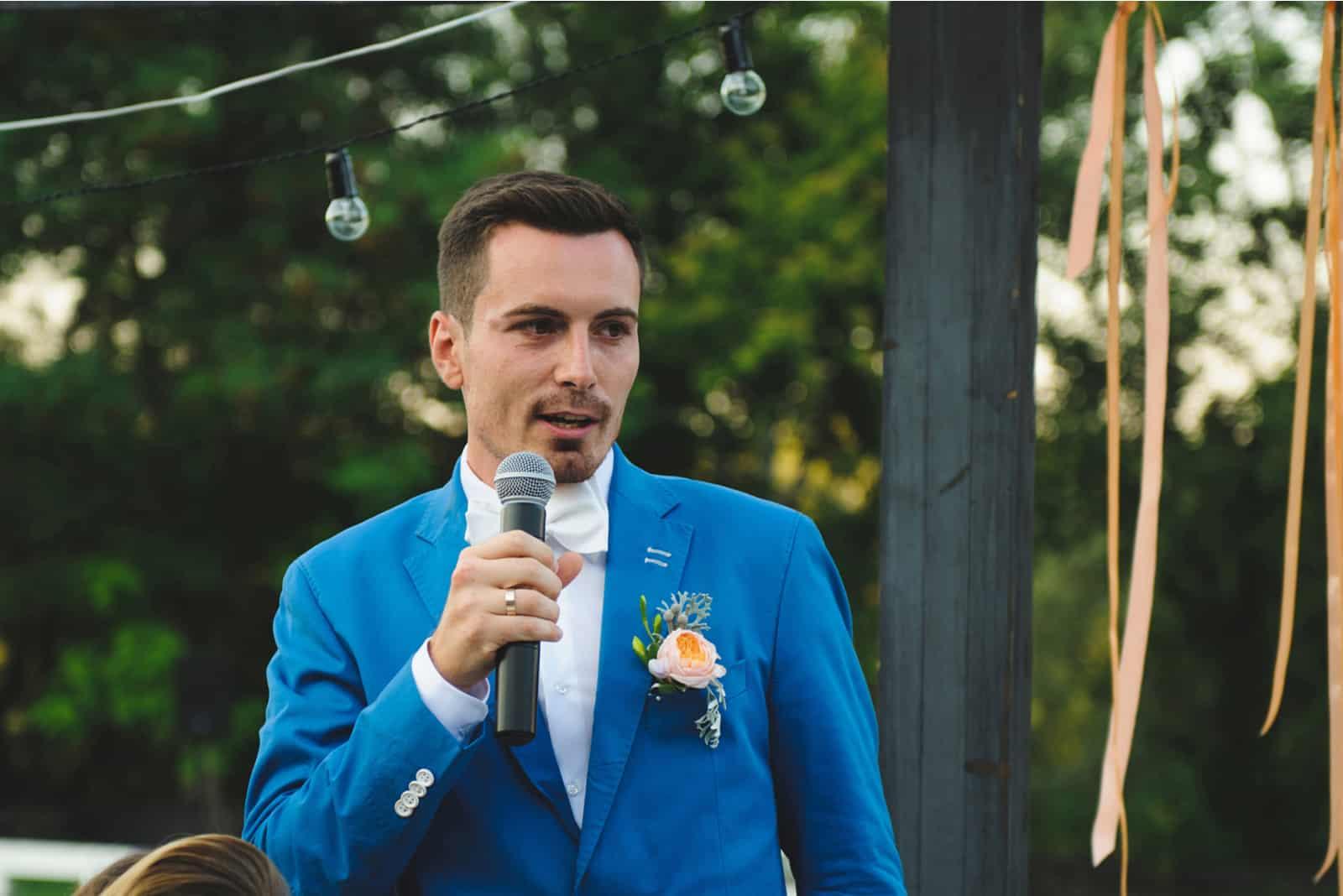 Bräutigam hält Mikrofon und spricht Sprache