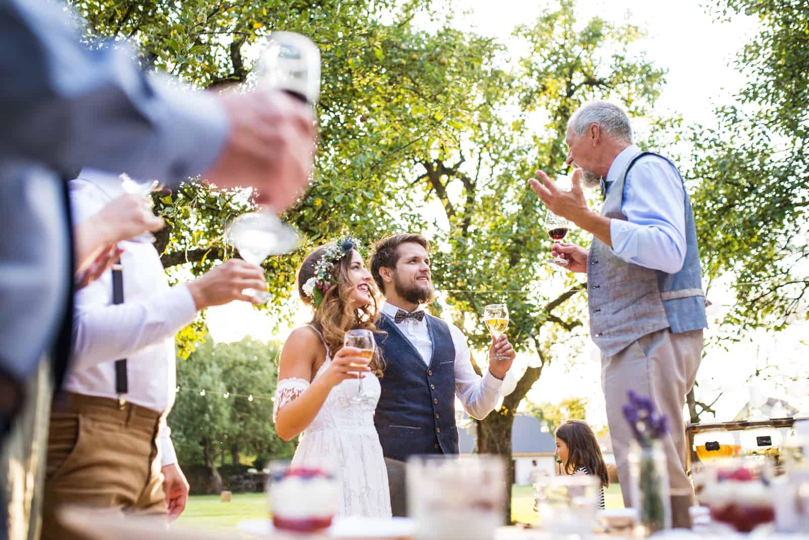 Ein älterer Mann, der Rede am Hochzeitsempfang draußen im Hintergrund macht.