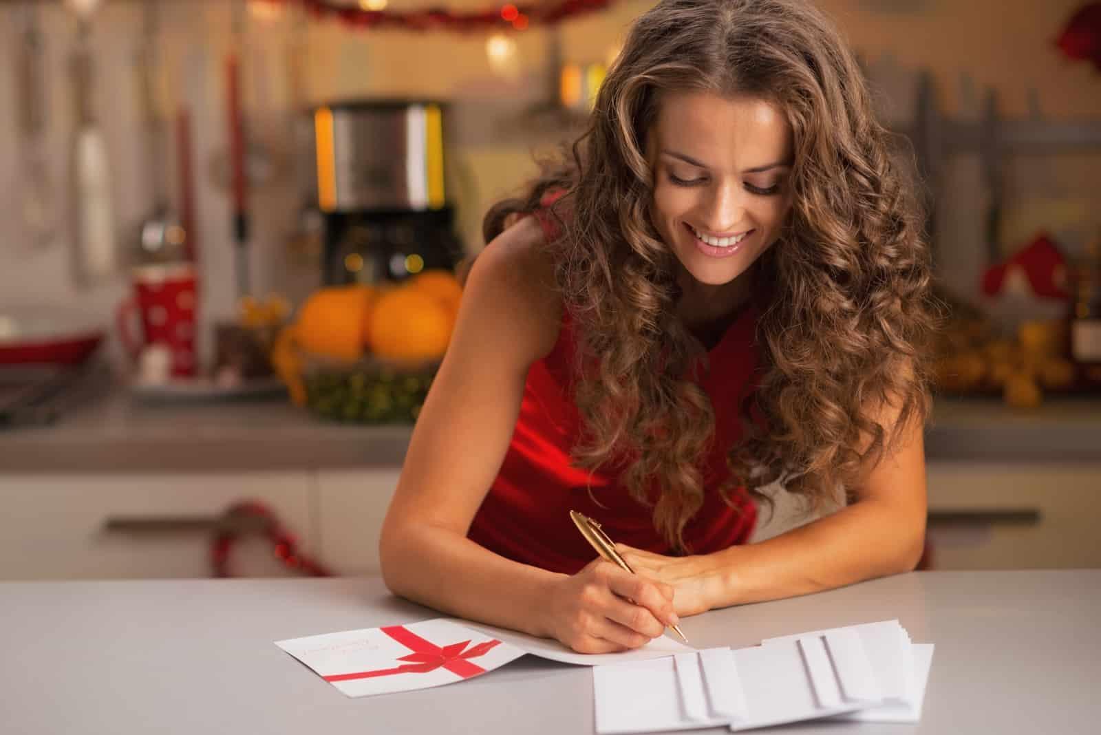 Glückliche junge Hausfrau, die Weihnachtspostkarten in der Küche signiert