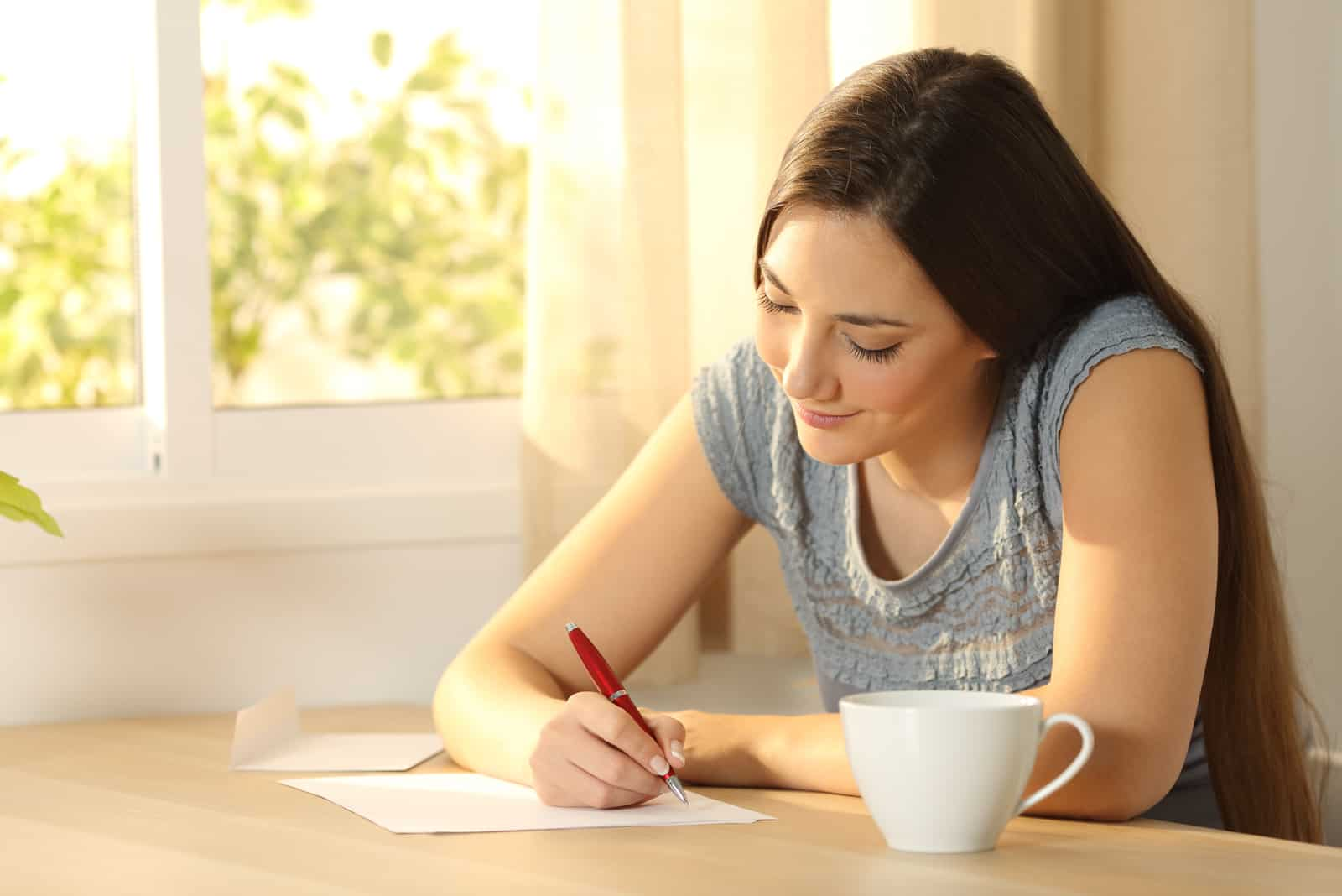 Glückliches Mädchen, das einen Brief auf einem Tisch zu Hause schreibt