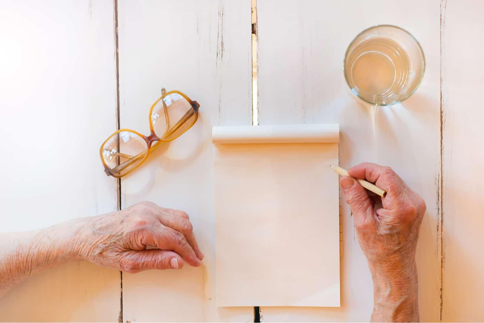 Hände der nicht wiedererkennbaren älteren Frau, die auf einem hölzernen weißen Schreibtisch schreibt