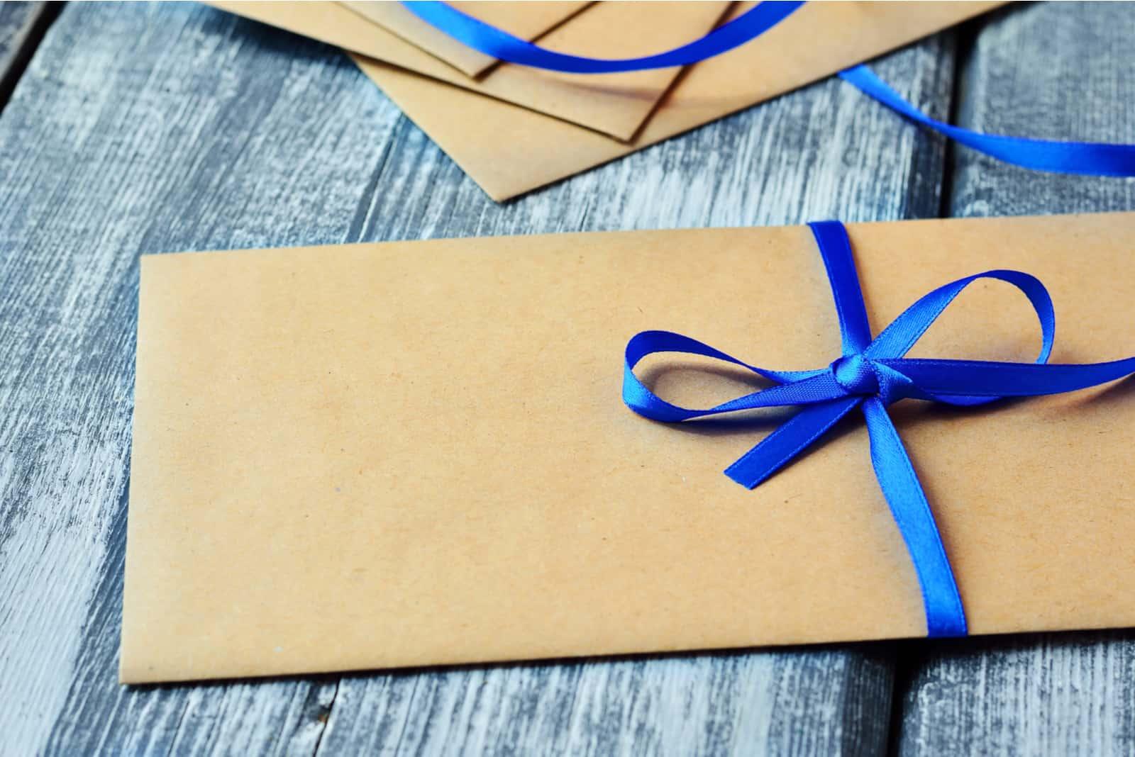Kraft-Umschlag mit blauem Band in einer Schleife gebunden