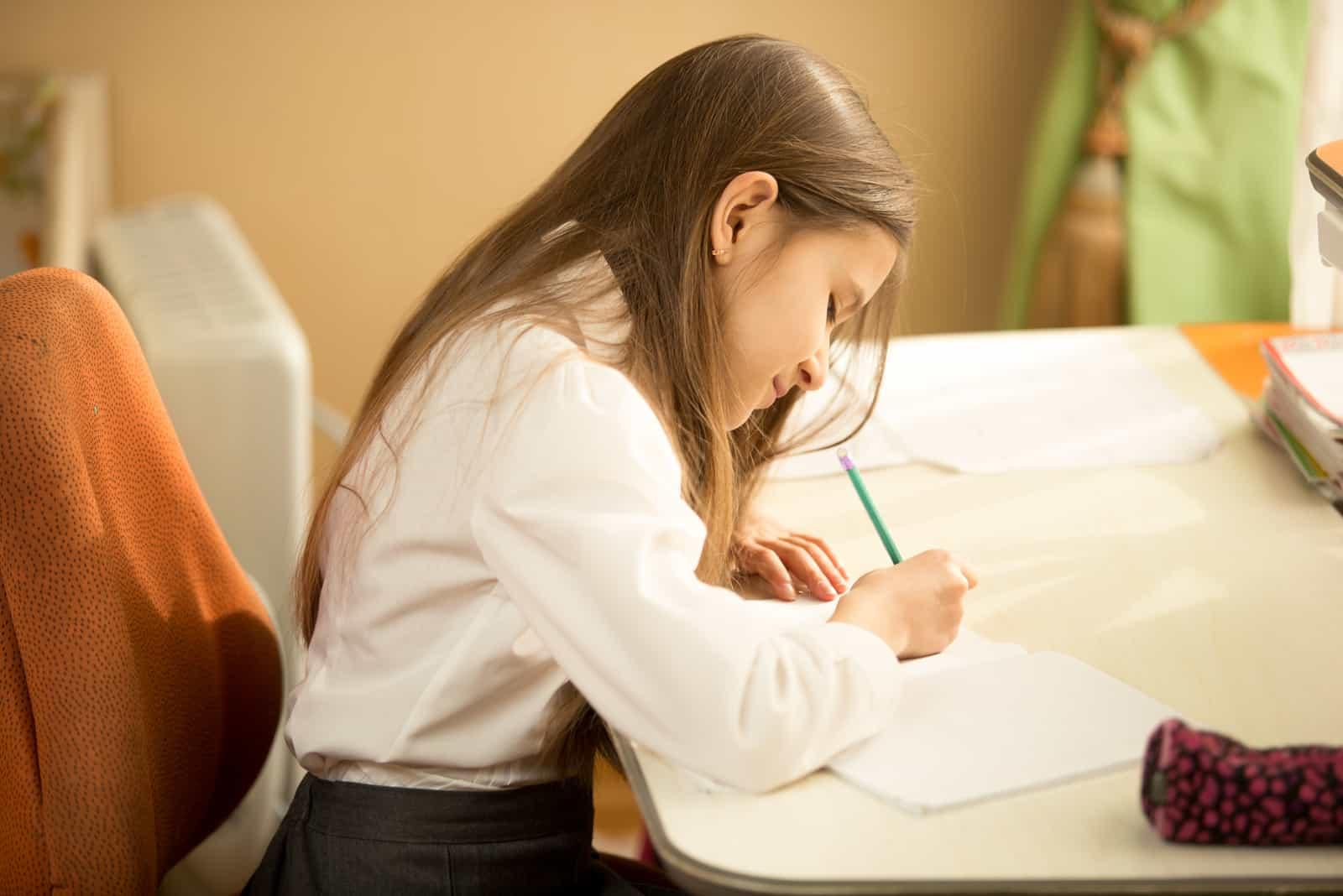 Mädchen, das im Notizbuch mit Bleistift an ihrem Schlafzimmer schreibt