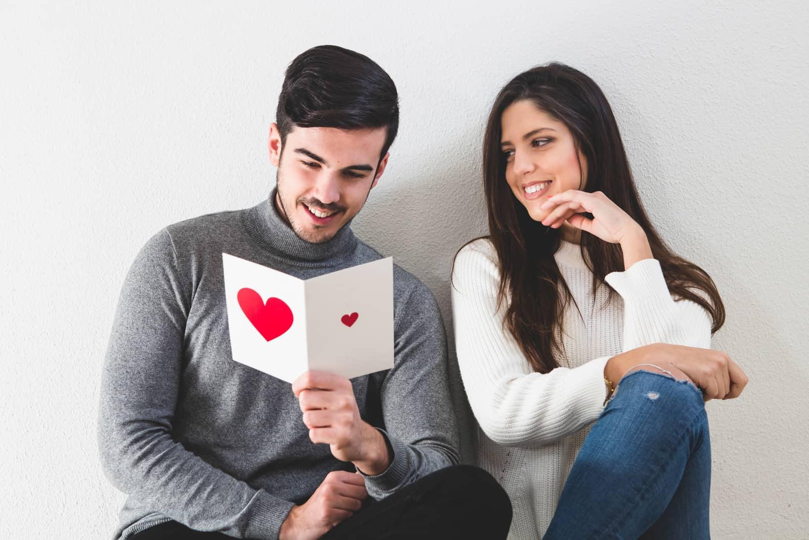 Nahaufnahme des glücklichen Paares im Bett mit Postkarte