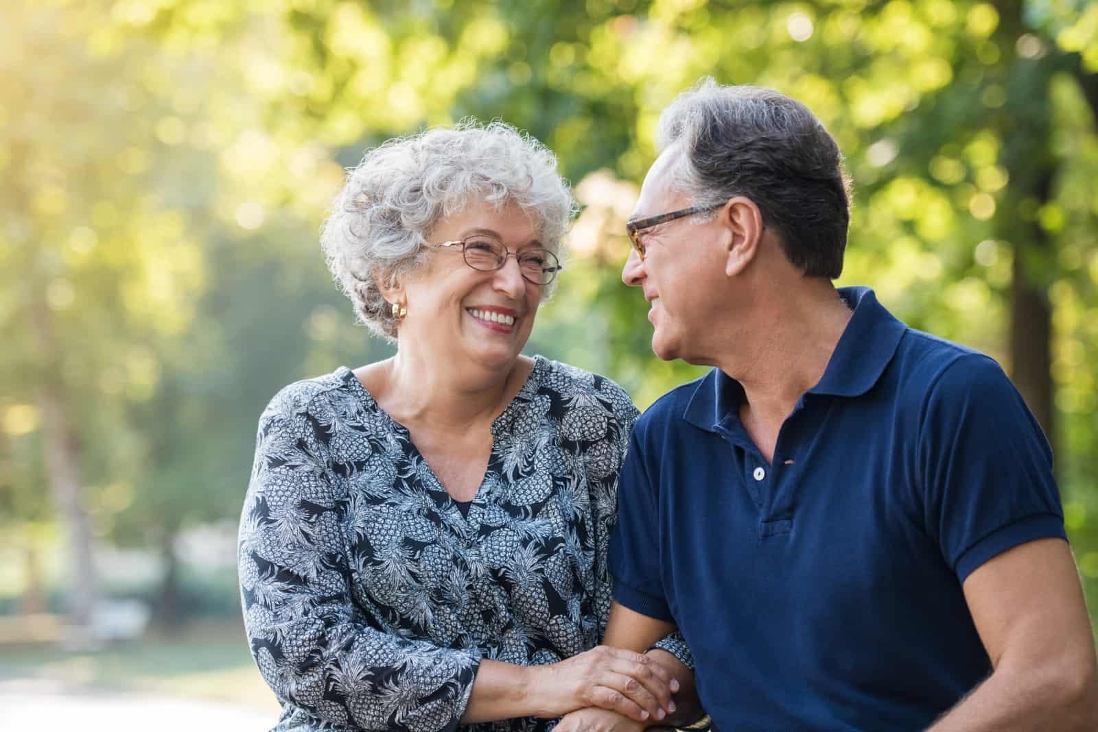 Porträt eines älteren Paares, das lächelt und einander im Park betrachtet.