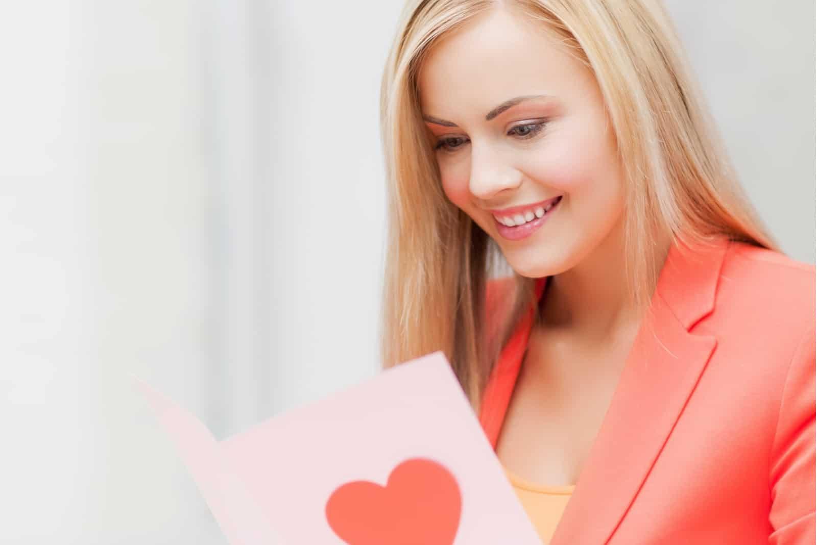 Bild der Frau, die Postkarte mit Herzform hält