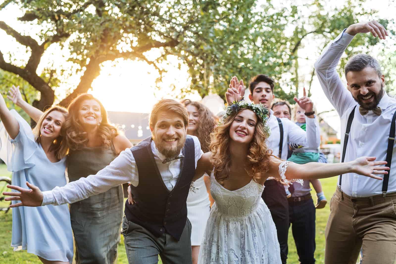 Braut, Bräutigam, Gäste posieren für das Foto bei der Hochzeitsfeier draußen im Hinterhof