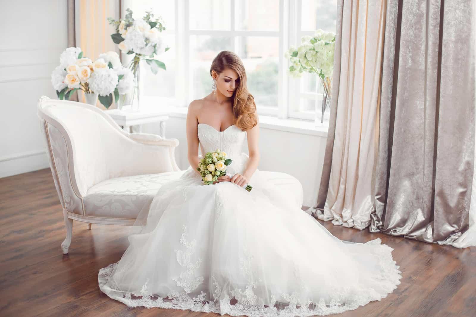 Braut im schönen Kleid sitzt auf Sofa drinnen