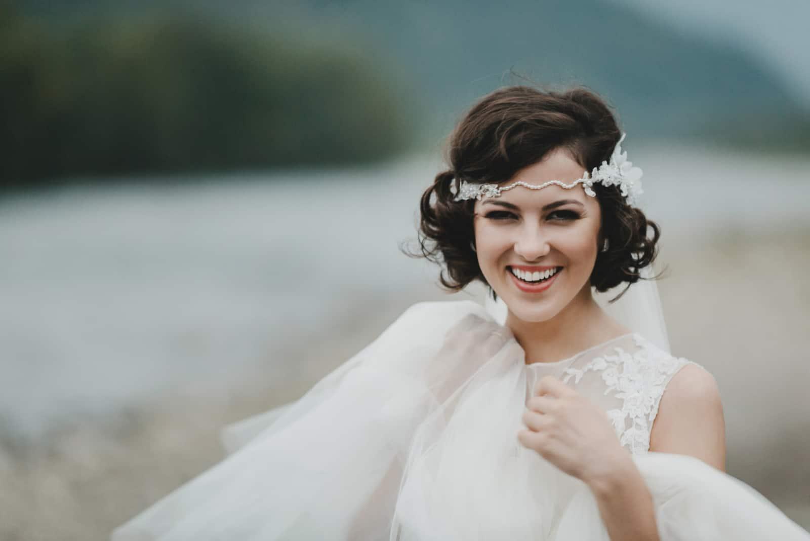 Braut mit kurzen brünetten Haaren lächelt