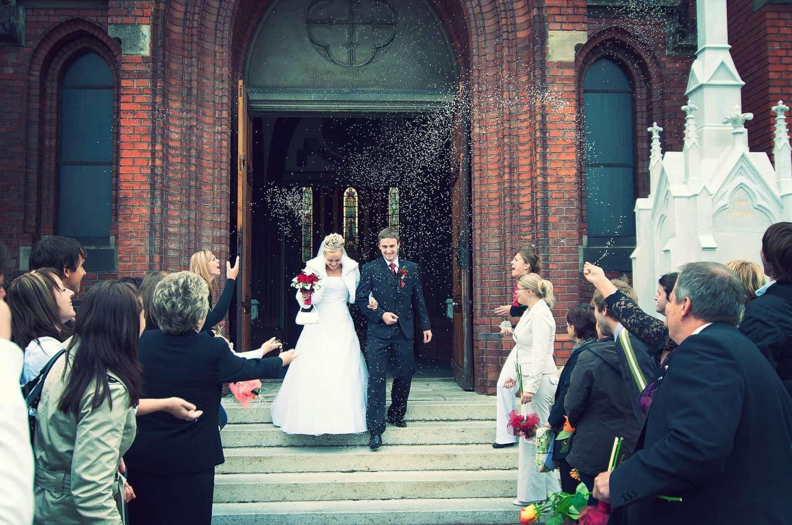 Braut und Bräutigam an der Kirchentür mit Reiskonfetti geworfen-1