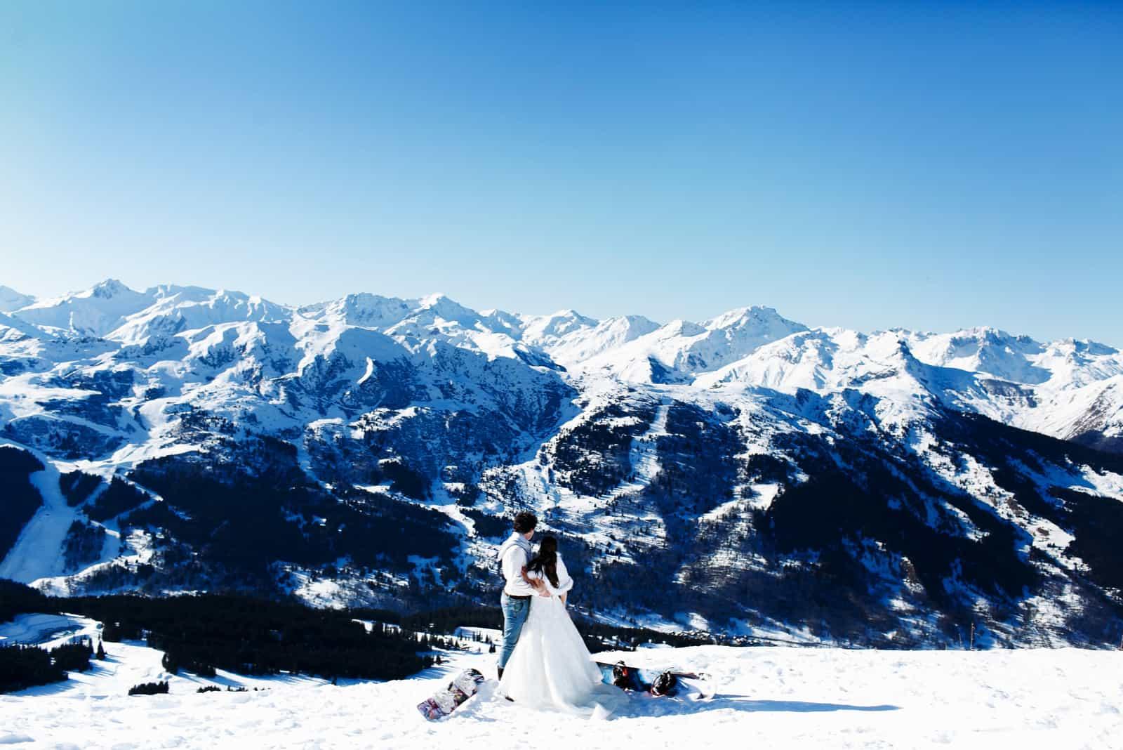 Braut und Bräutigam in Liebe küssen auf dem Hintergrund der Alpen Courchevel