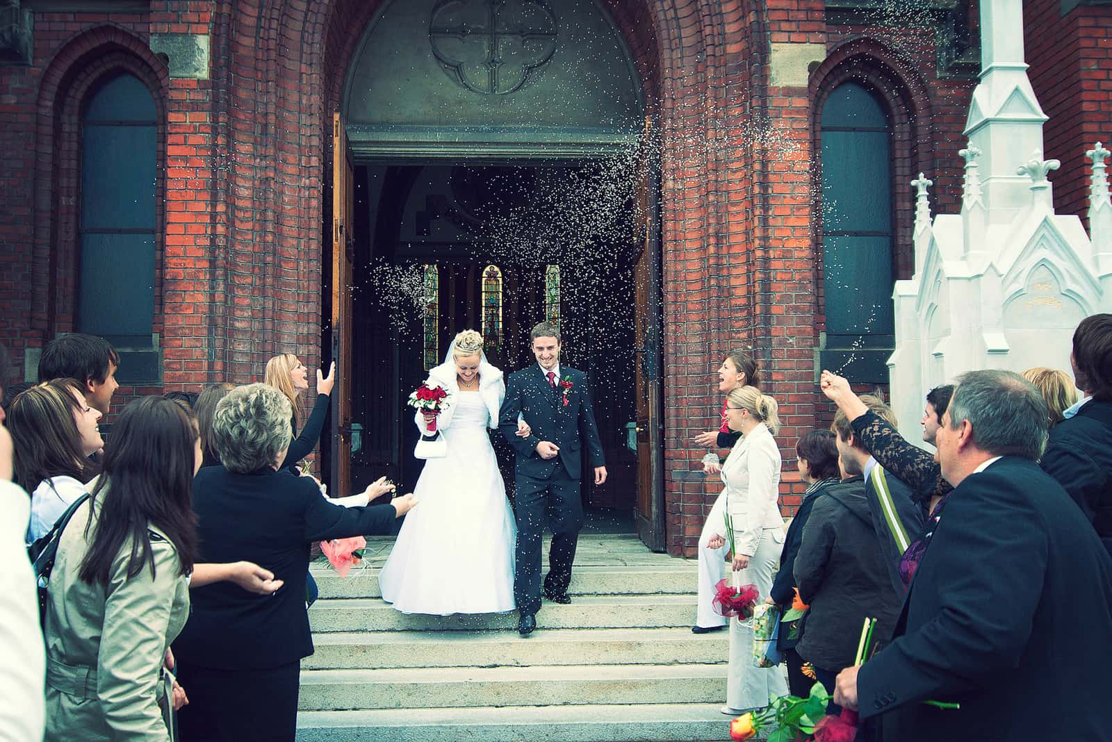Braut und Bräutigam an der Kirchentür mit Reiskonfetti geworfen