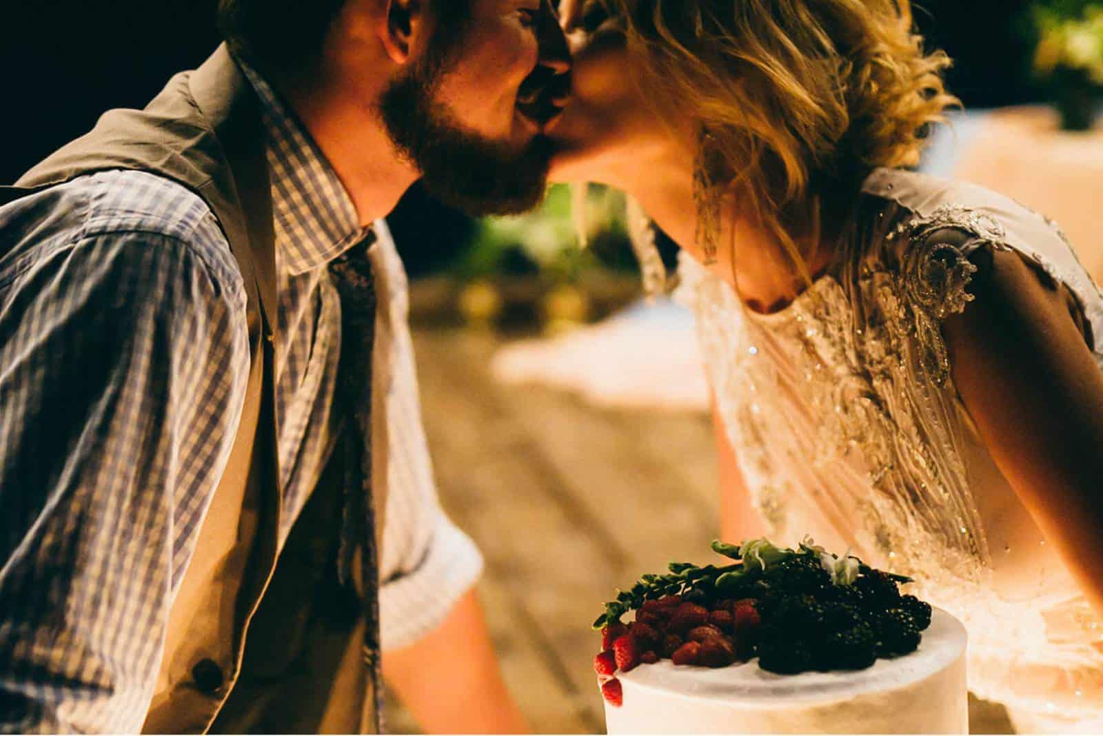 Braut und Bräutigam küssen nahe Hochzeitstorte.
