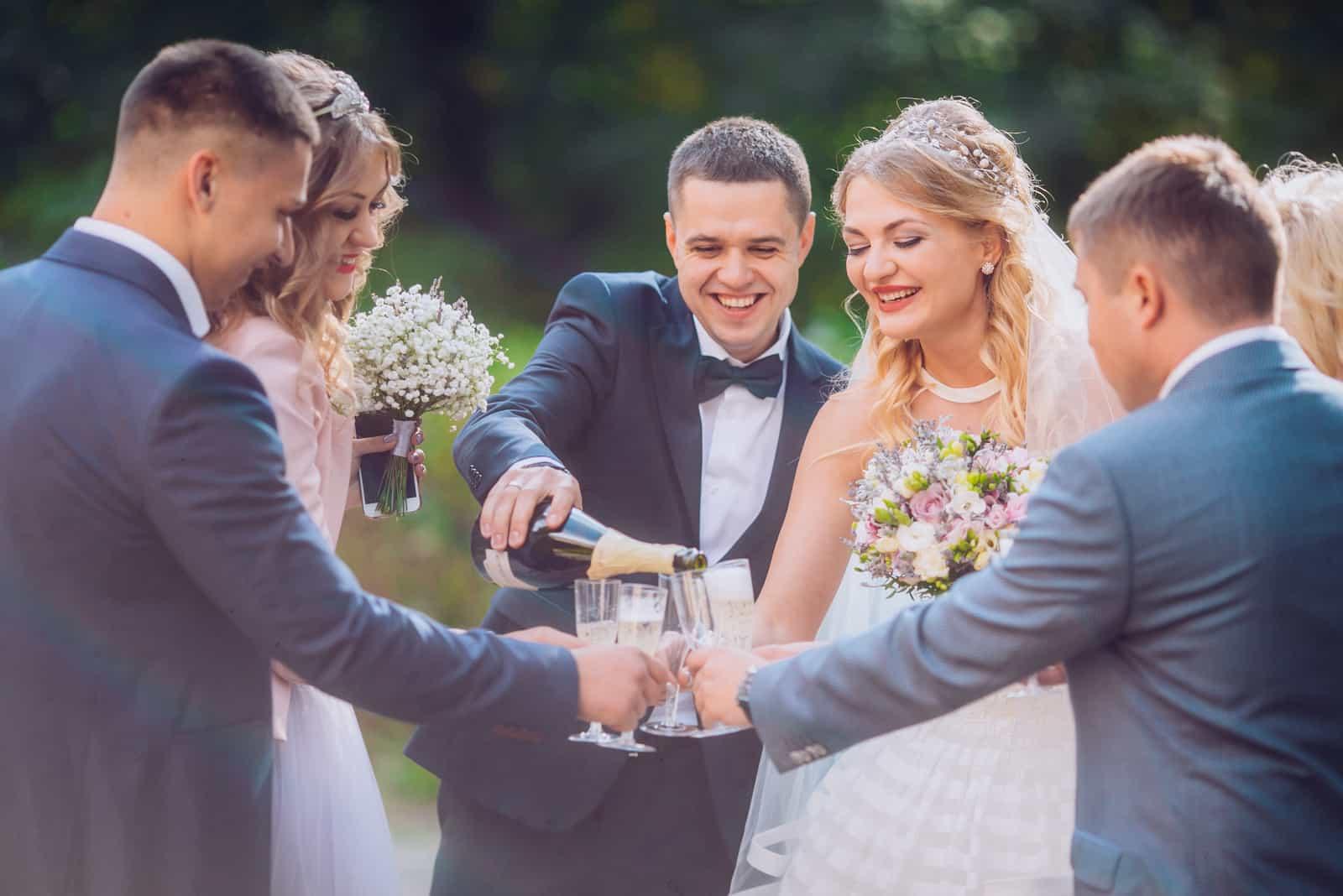 Braut und Bräutigam mit glücklichen Trauzeugen und Brautjungfern, die Spaß haben