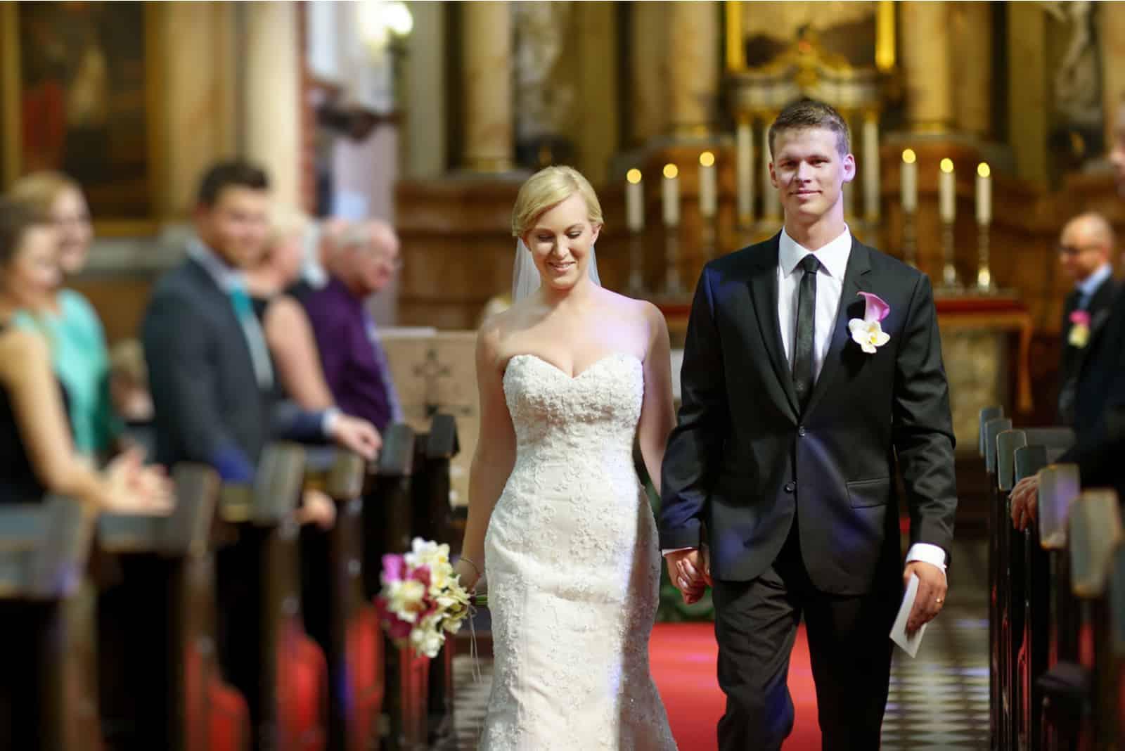 Braut und Bräutigam verlassen die Kirche nach einer Hochzeitszeremonie