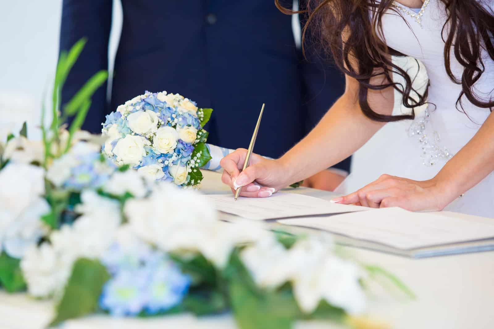 Brauthand mit einem Stift, der Hochzeitslizenz unterzeichnet (1)