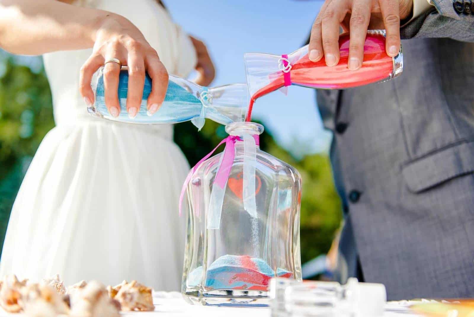 Bräutigam und Braut setzen Sand in Flasche