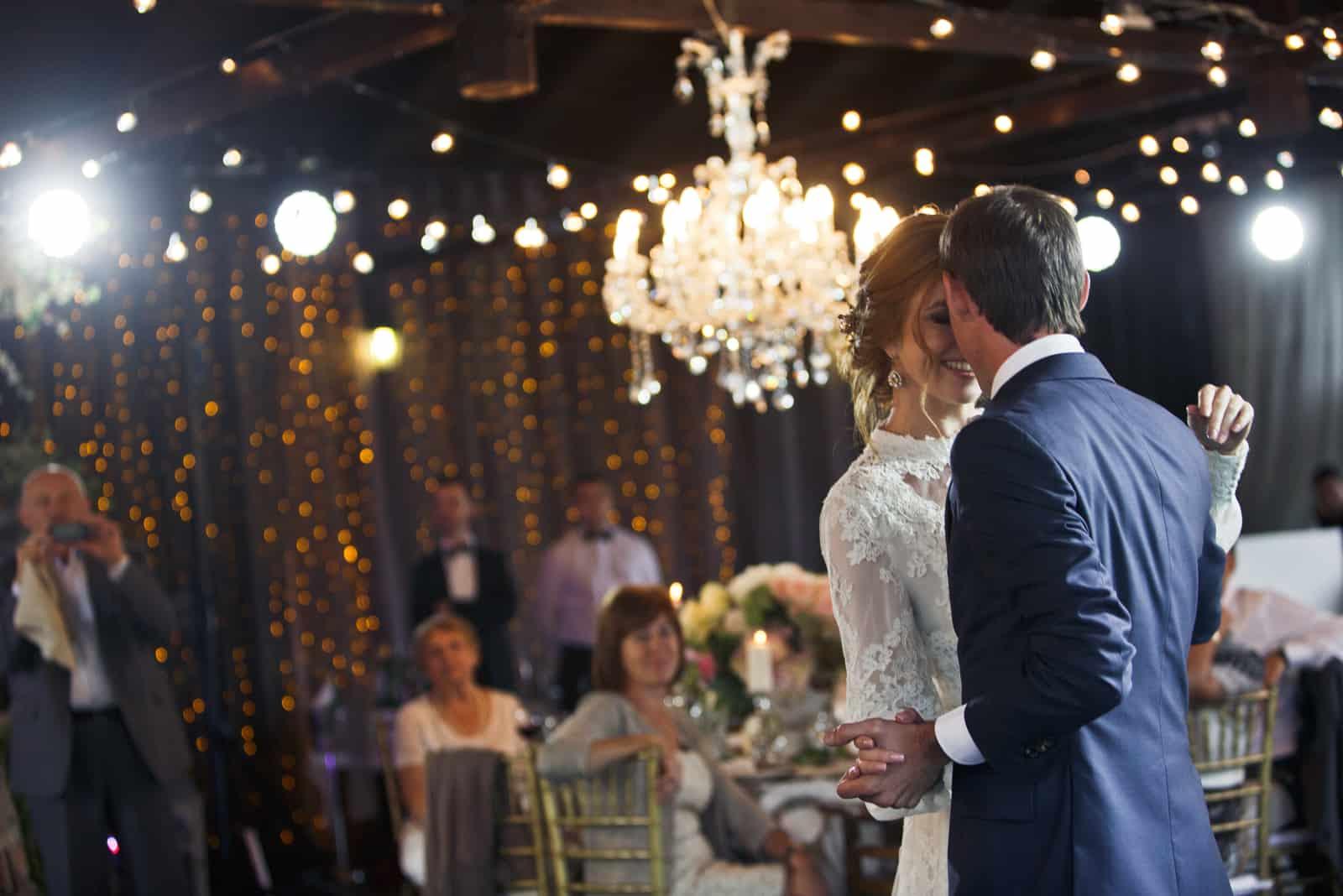 Der Bräutigam hält die Hand der Braut und tanzt mit ihr mitten in einem Restaurant