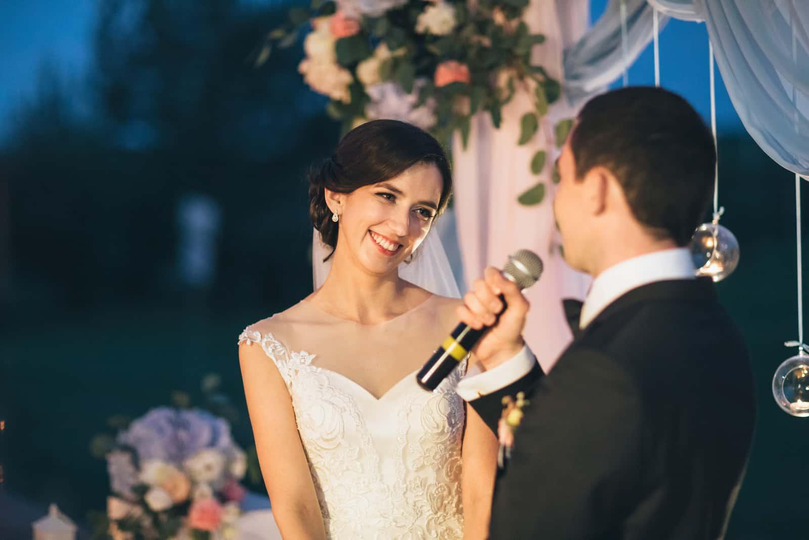 Der Bräutigam hält ein Mikrofon und spricht mit seiner Braut