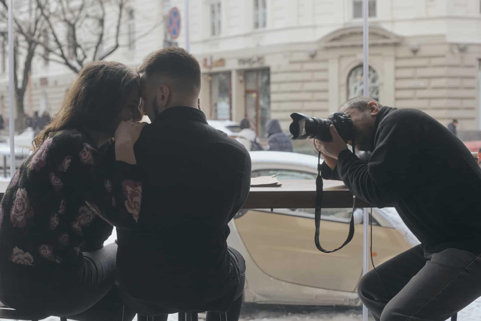 Der Fotograf fotografiert ein schönes und glückliches Paar in einem Café