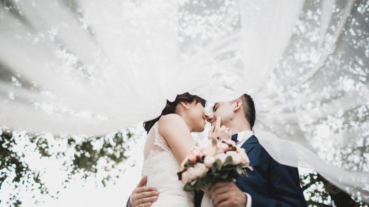 Das Brautpaar umarmt und küsst sich