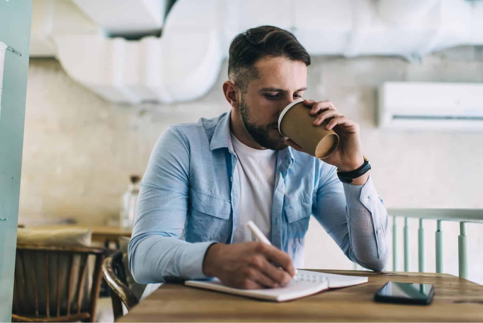 Ein Mann sitzt, trinkt Kaffee und schreibt