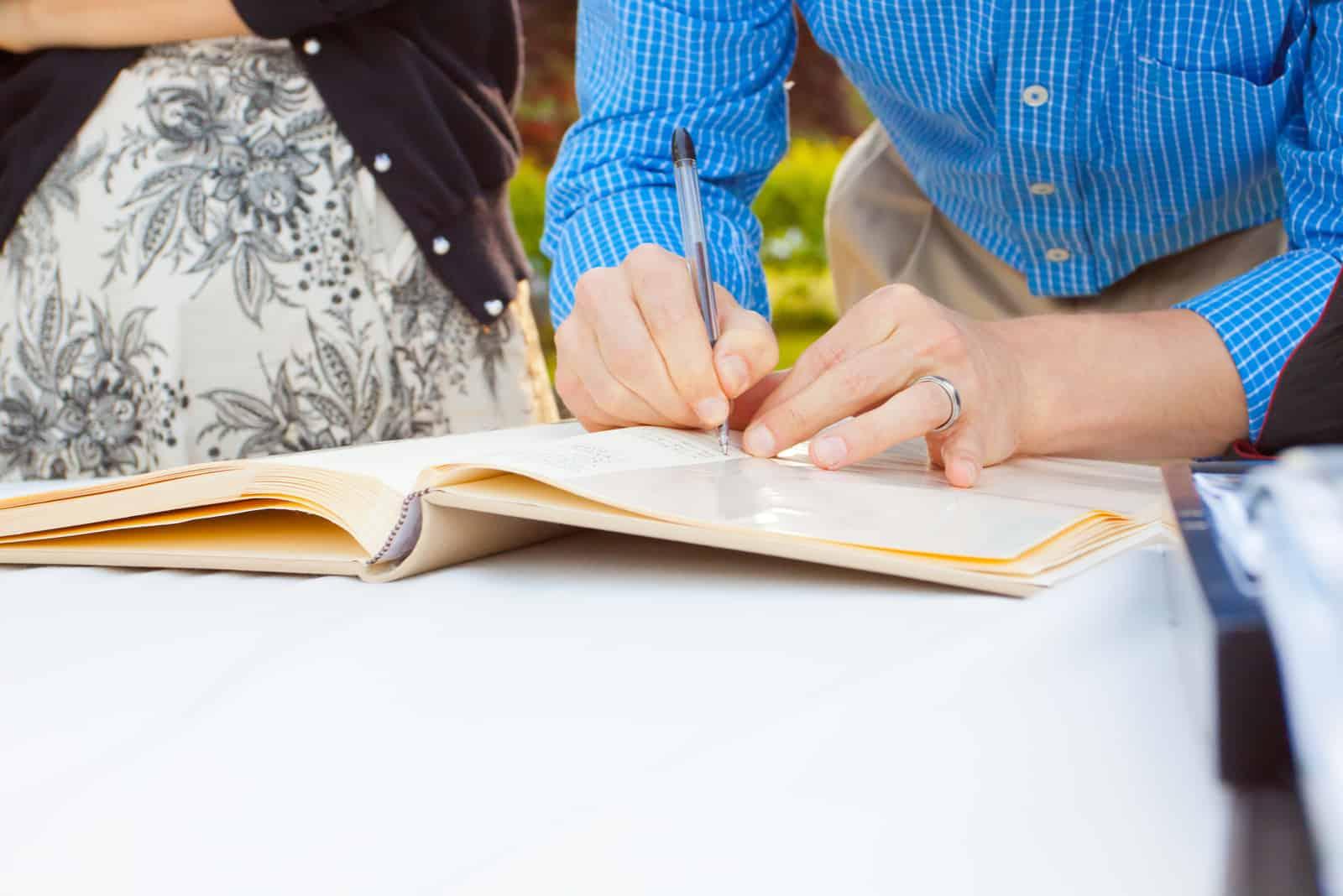 Ein Mann und eine Frau unterschreiben ein Hochzeitsgästebuch mit einem Stift.