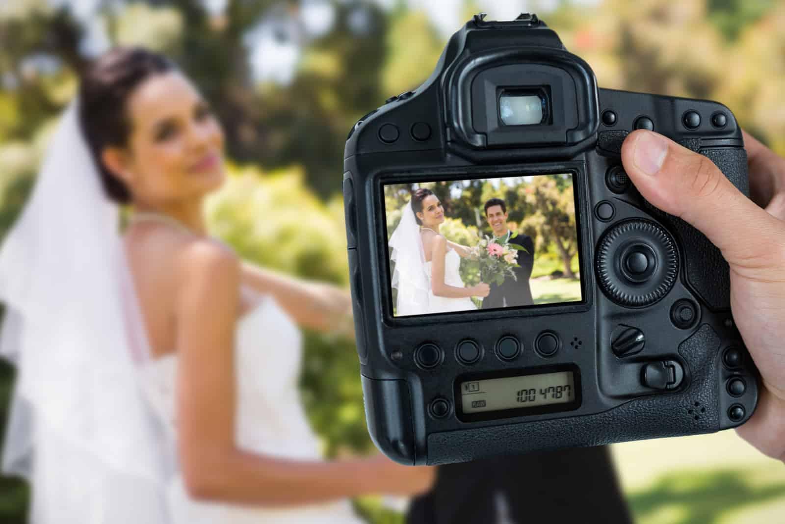 Fotograf hält Kamera gegen glückliches frisch verheiratetes Paar mit Blumenstrauß