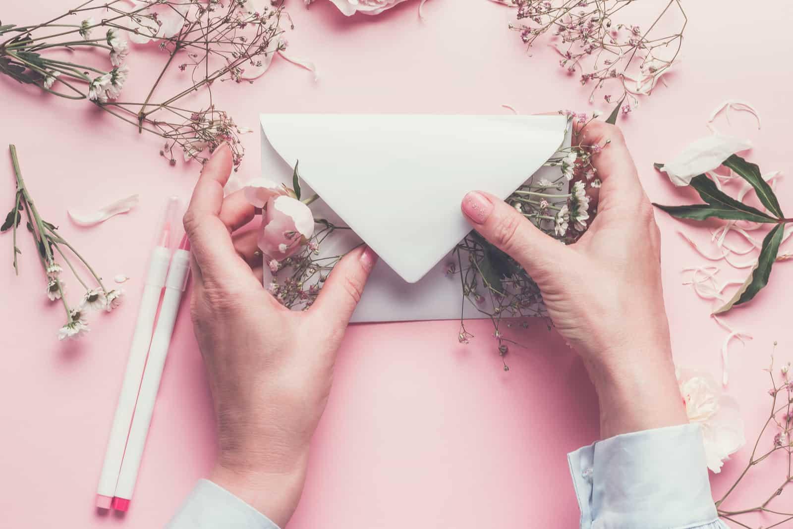Frauenhände, die Papierumschlag mit Blumen gefüllt halten
