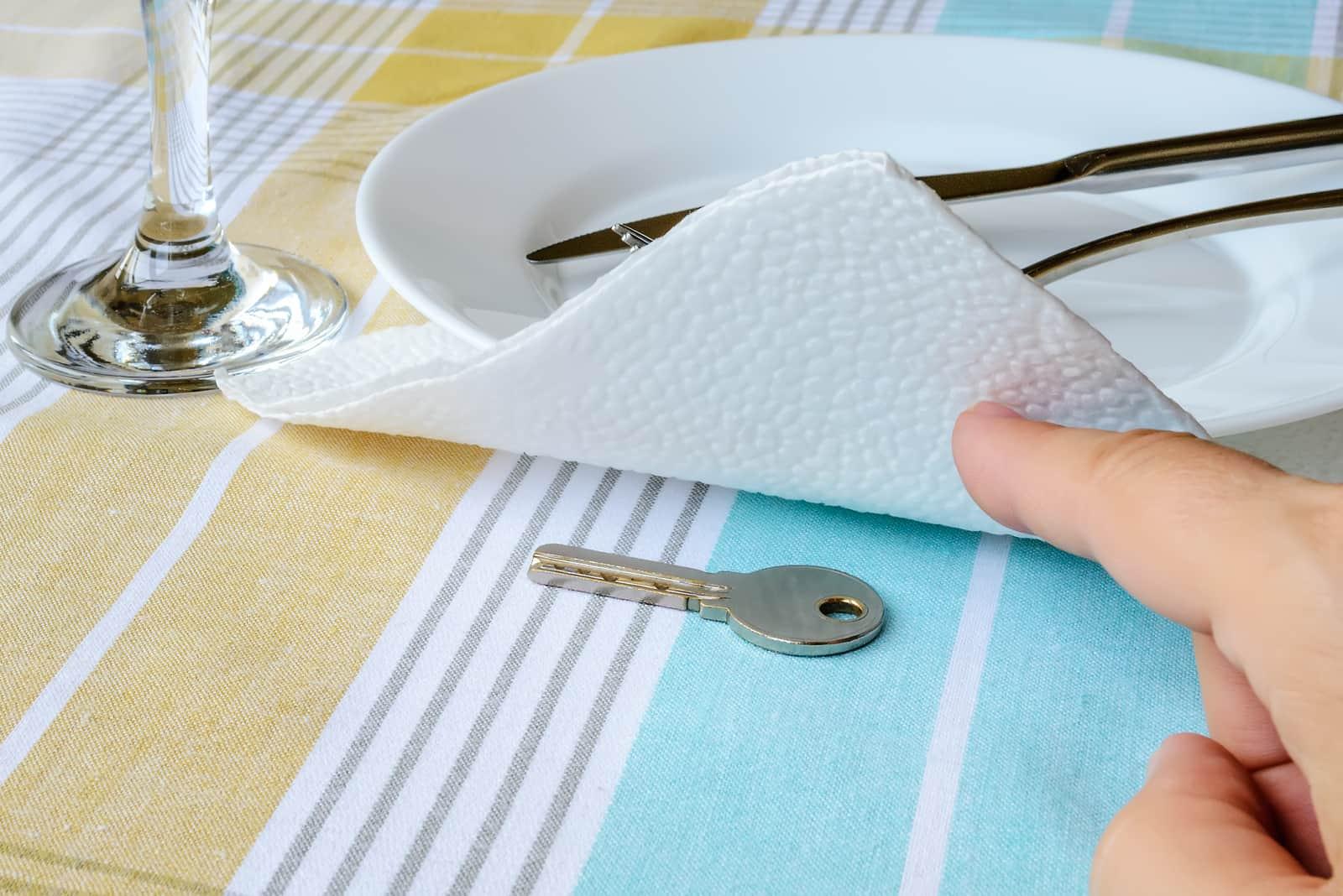 Frauenhand zeigt den Schlüssel unter der Papierserviette nahe weißem Teller auf dem Esstisch
