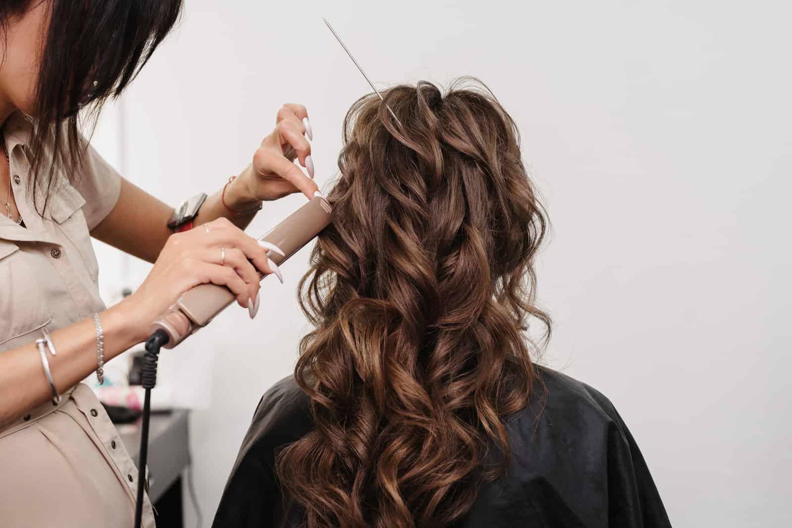 Friseur in einem Schönheitssalon macht eine Frisur für ein Mädchen Braut