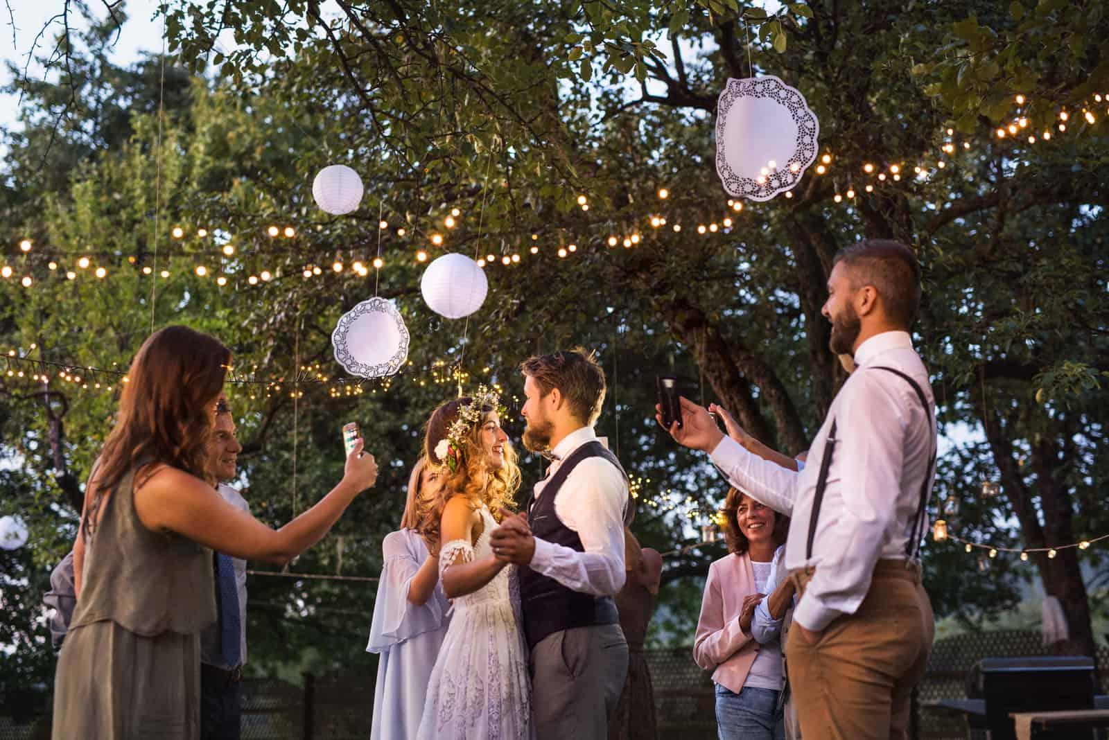 Gäste mit Smartphones fotografieren Braut und Bräutigam auf der Hochzeitsfeier draußen