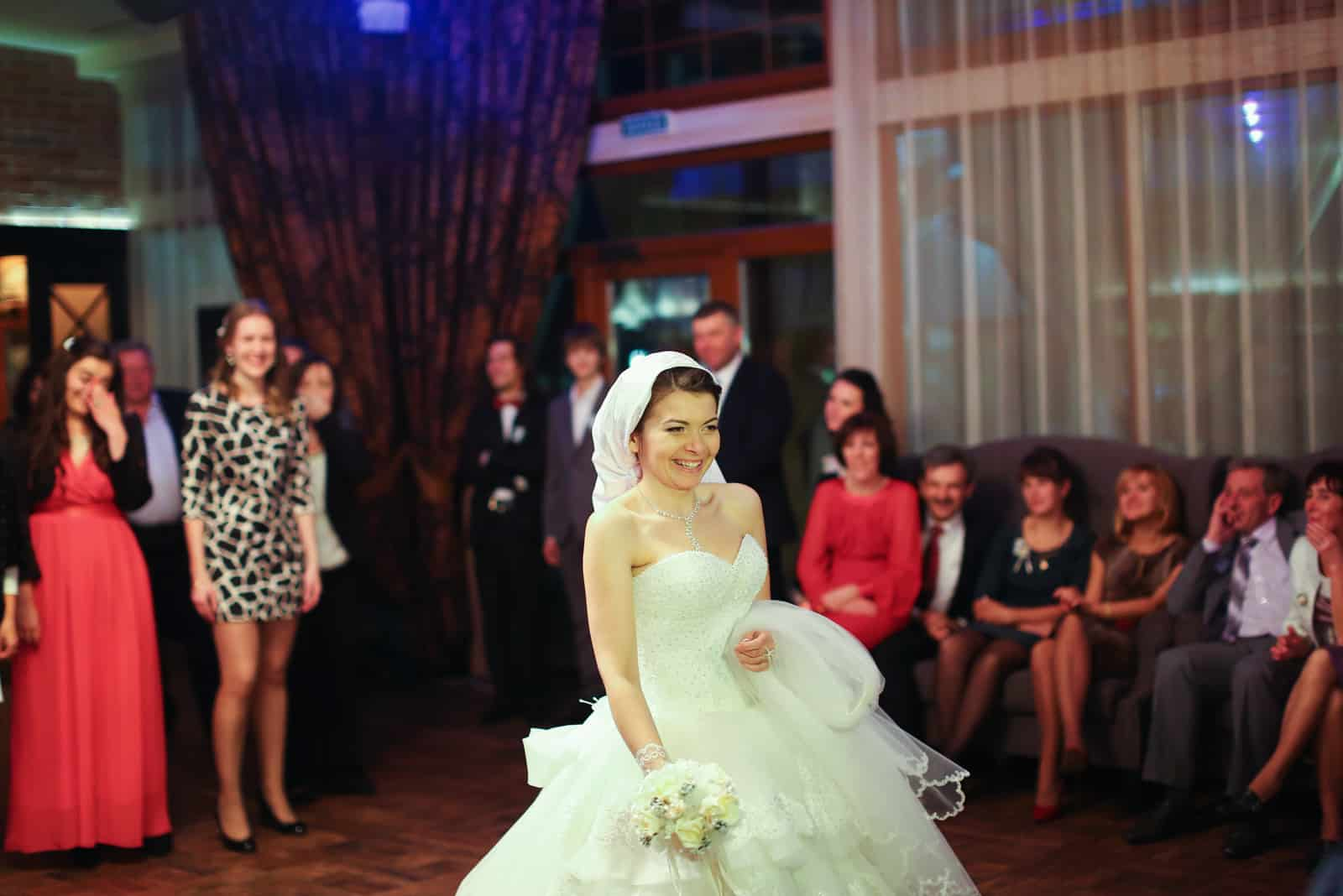 Glückliche Braut wirft Blumenstrauß