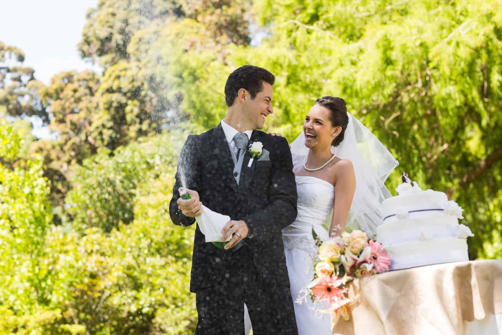 Glückliches junges frisch verheiratetes Paar mit Bräutigam, der die Champagnerflasche am Park öffnet