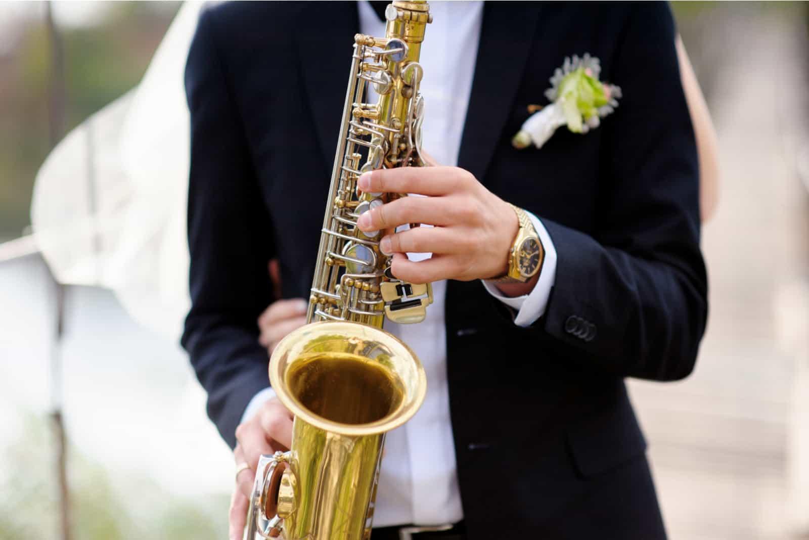 Hände des Bräutigams spielen auf Saxophon