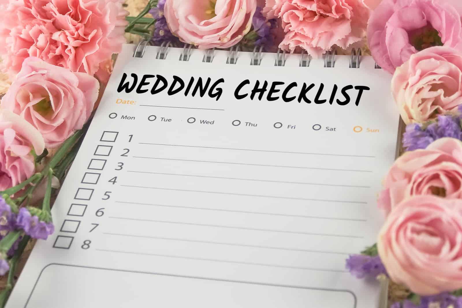Hochzeitscheckliste Notizpapier auf rosa Blumenhintergrund