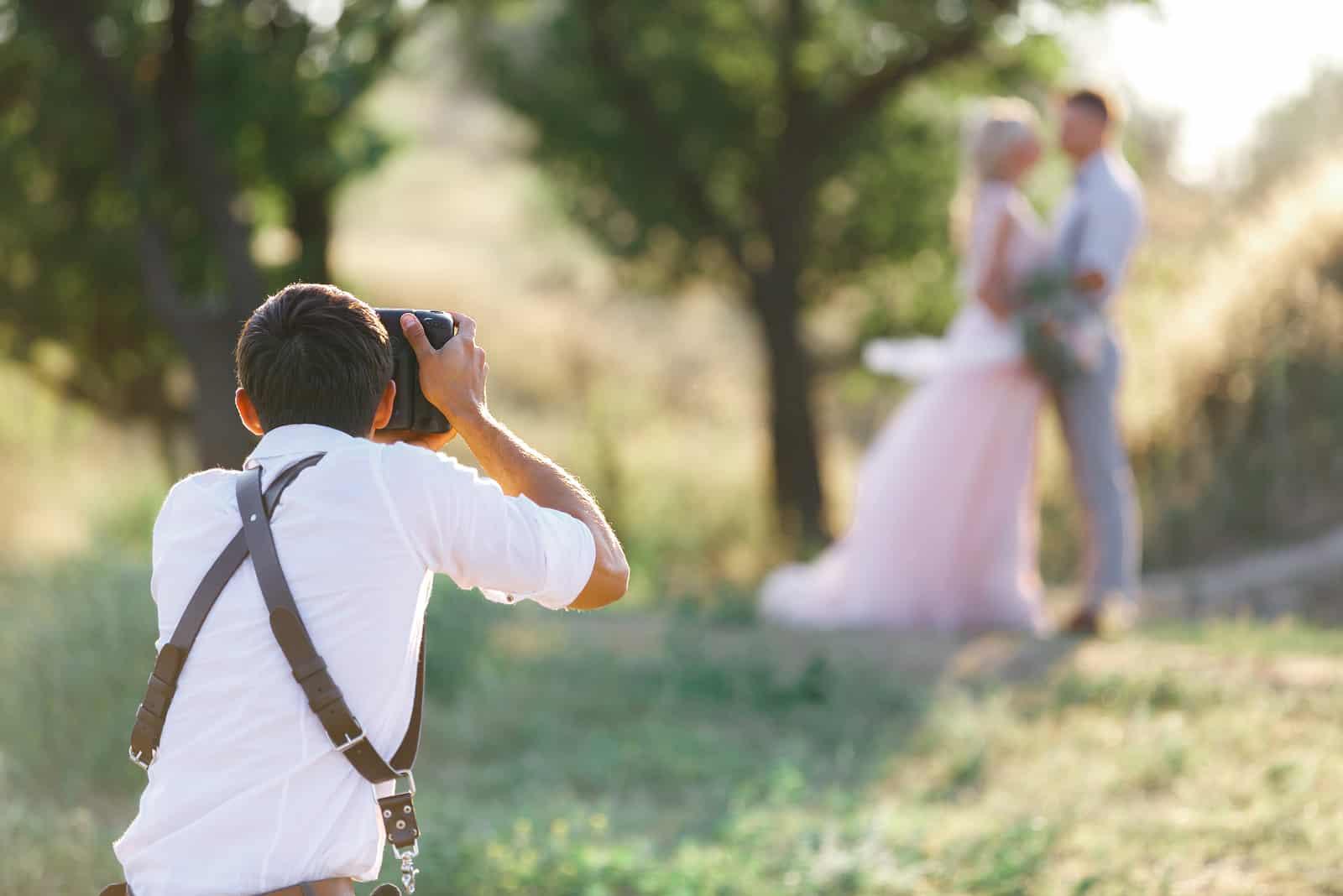 Hochzeitsfotograf fotografiert Braut und Bräutigam in der Natur
