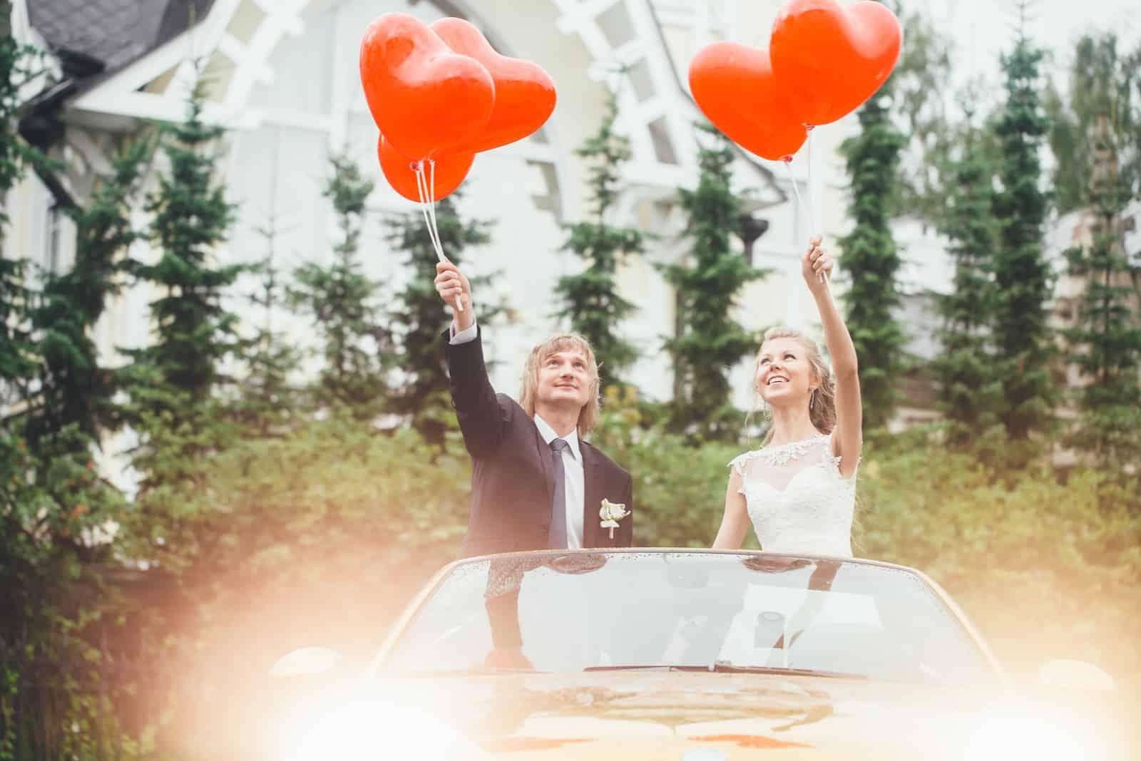 Hochzeitspaar im Auto mit Luftballons in den Händen