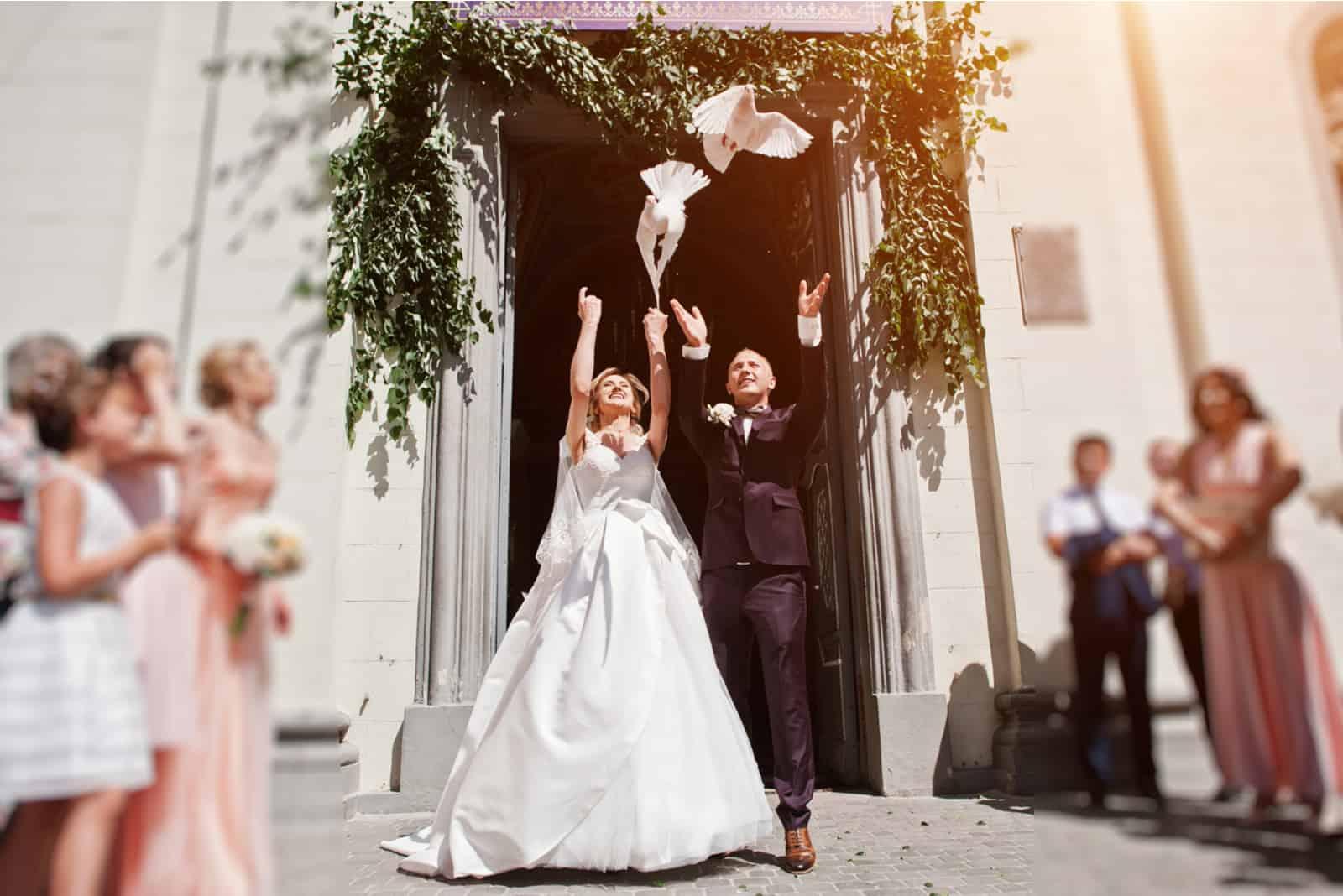 Hochzeitspaar mit freisetzenden Tauben in den Himmel gegen Kirchentor