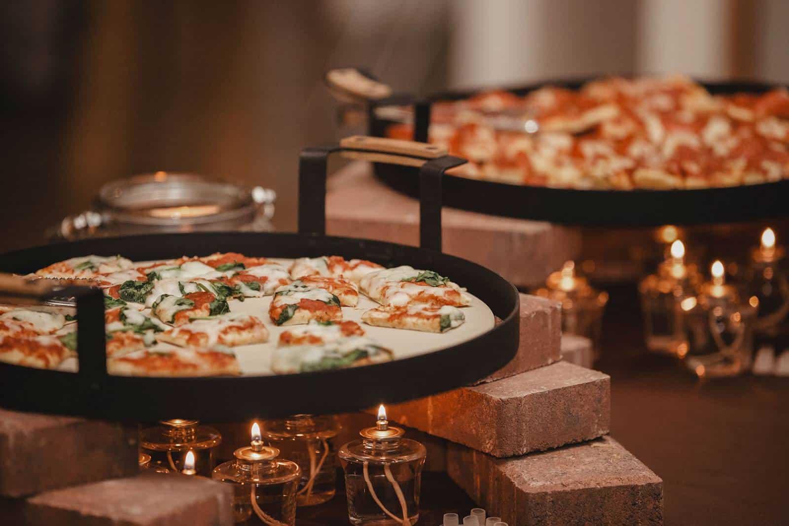Hochzeitspizza und Kerzen auf dem Tisch