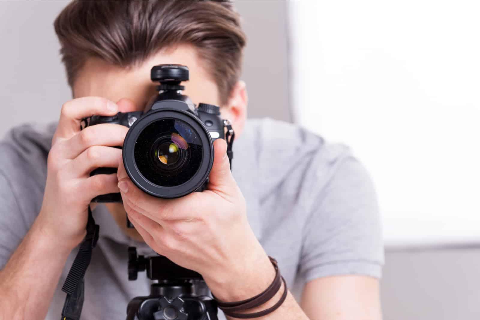 Junger Mann, der Sie mit Digitalkamera beim Stehen im Studio fokussiert